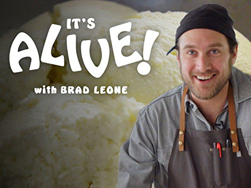 "Brad Leone of Bon Appetit's ""It's Alive!"" Leone is dressed in a  grey collared shirt and brown apron, with the stylised text ""It's Alive! with Brad Leone"" in bold white letters beside him."