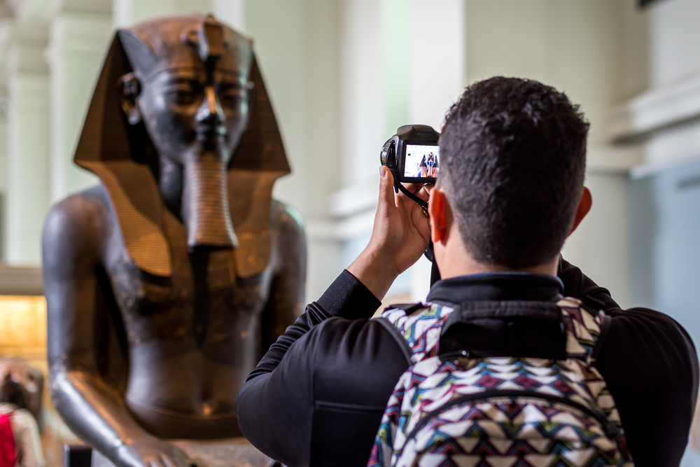 Man takes picture of Egyptian statue in a museum
