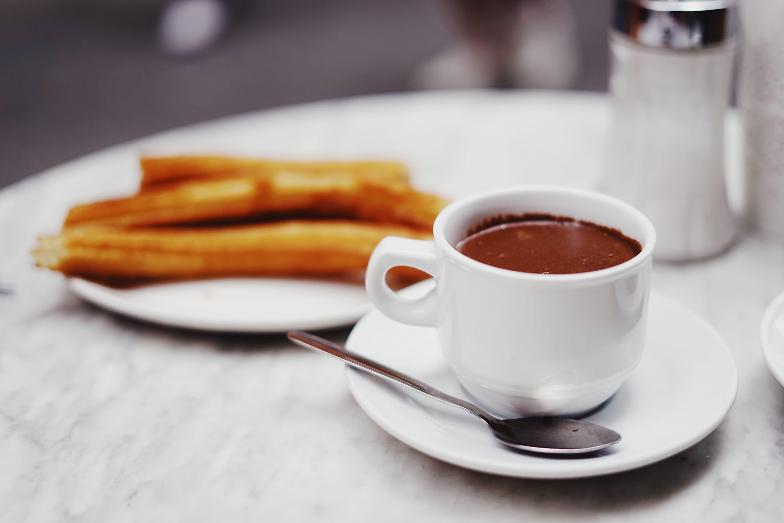 Out of focus churros with hot chocolate for dipping in the foreground