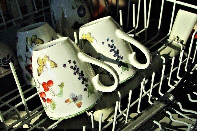 mugs on top of a dishwasher rack