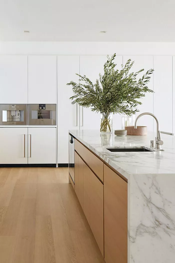 large modern kitchen with white cabinets and marble waterfall countertop