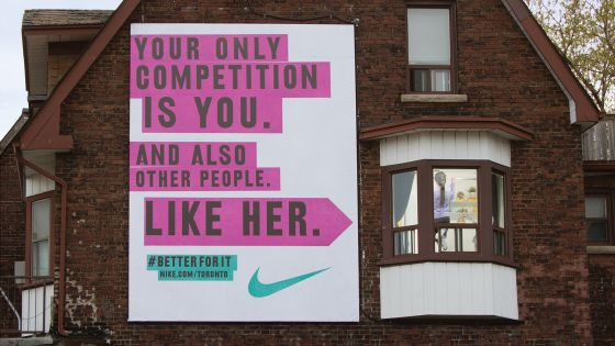 "A Nike billboard advertisement with the message ""Your only competition is you. And also other people. Like her. #BetterForIt""."