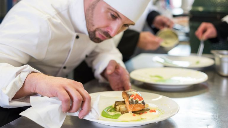 Chef carefully plating a dish to match his mission statement of beautiful presentation.