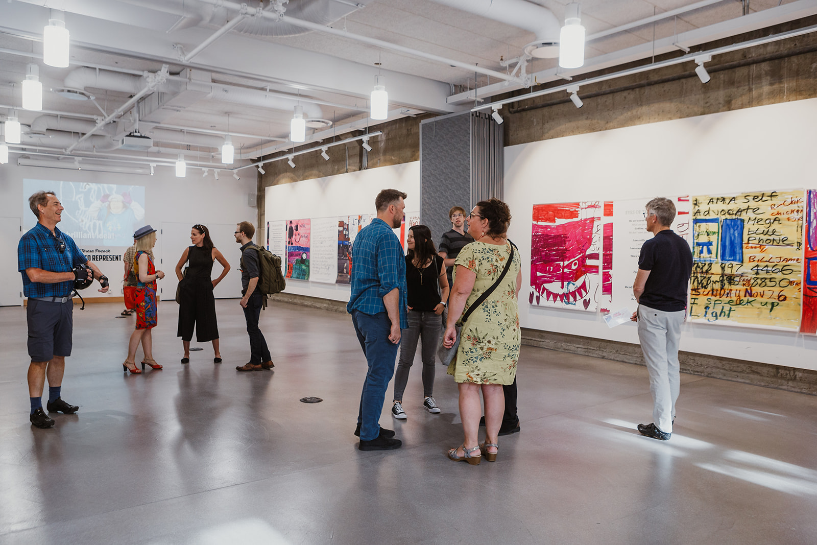 Groups of people are engaged in conversation at the opening of Born To Represent on July 22, 2019. Teresa's large colorful artwork hangs along one wall. Photo by Isabella Sarmiento, This Is It Studios.