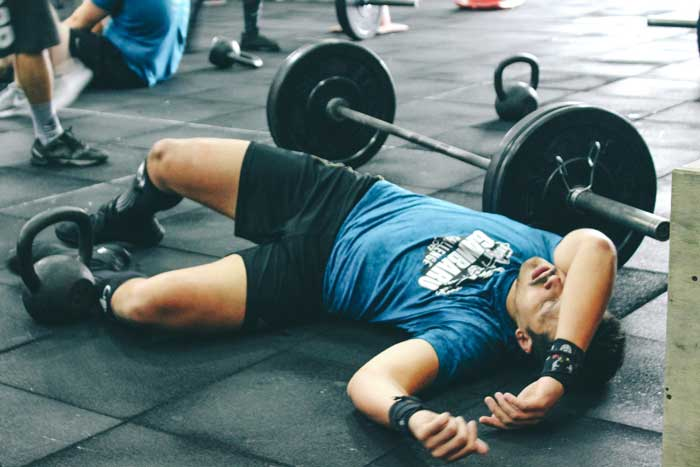 man resting on the ground next to barbell and weights
