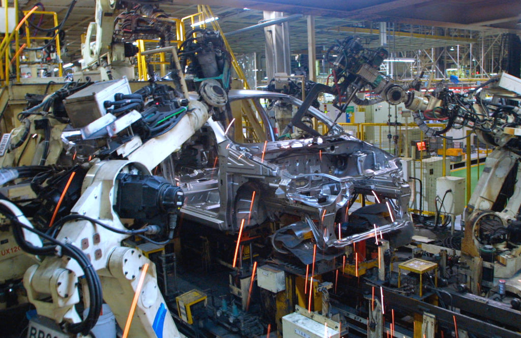 Robots assemble a new General Motors Daewoo vehicle, the KALOS, at the Bupyung plant October 28, 2002 in Inchon, South Korea. Keith Krach was the youngest Vice President in General Motors' history and founded one of the company's earliest robotics lines before moving on to Silicon Valley.
