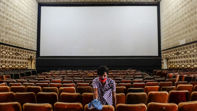 A worker cleans the seats in a cinema hall as part of preparations for a possible reopening after the government eased the lockdown restrictions previously imposed due to the Covid19 Corona virus, in Chennai on October 8, 2020. (Photo by Arun SANKAR / AFP) (Photo by )