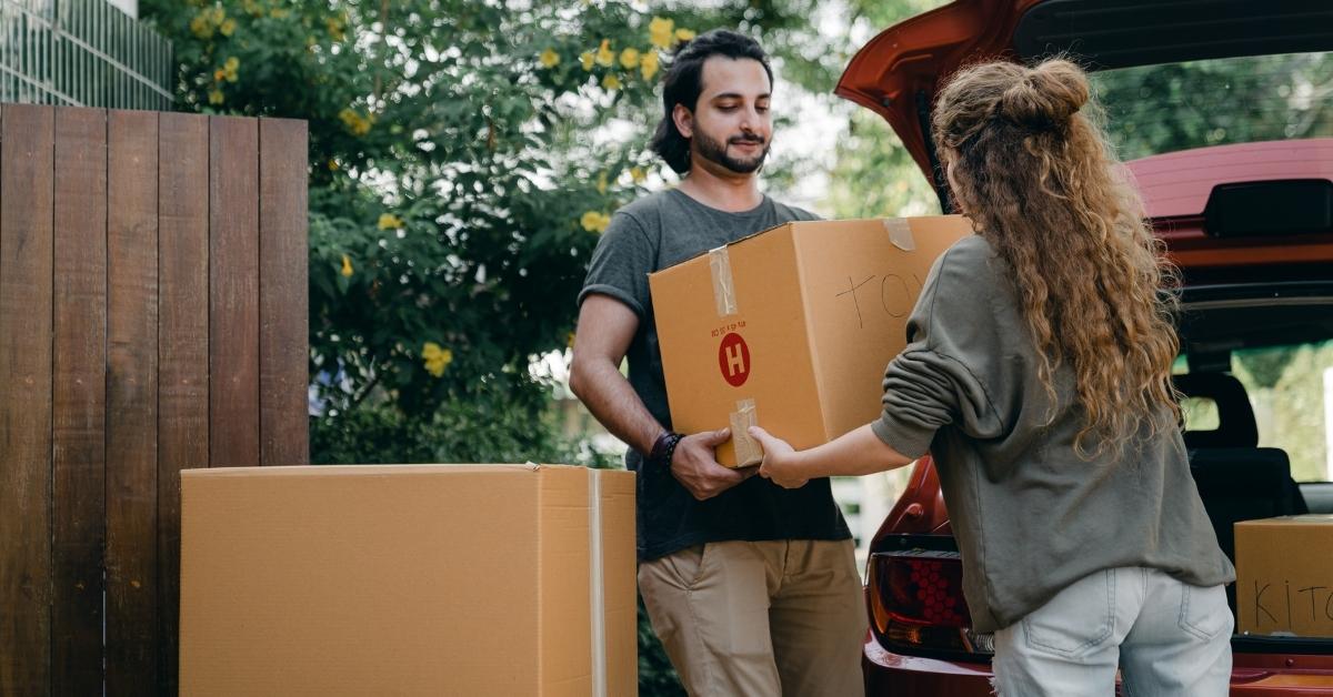 muž podáva žene škatuľu pri sťahovaní do nového domu