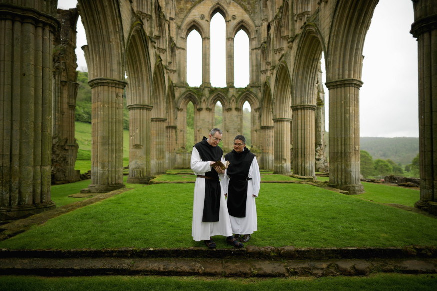 THIRSK, ENGLAND - MAY 26:    Cistercian Monks, Father Joseph and Brother Bernard John (R) read from a 500-year-old prayer book as they visit the ruins of Rievaulx Abbey in North Yorkshire on May 26, 2016 in Thirsk, England. The monks were visiting the Abbey to view the new exhibition centre and museum at the English Heritage site, which tells the story of Rievaulx from its foundation in 1132 to its suppression by Henry VIII. Rievaulx Abbey was the first monastery of the reforming Cistercian order in the North of England.  At its peak in the 1160's it was home to a community of over 600 men, who passed their lives in an ordered daily sequence of religious services, reading and manual work.  (Photo by Christopher Furlong/Getty Images)