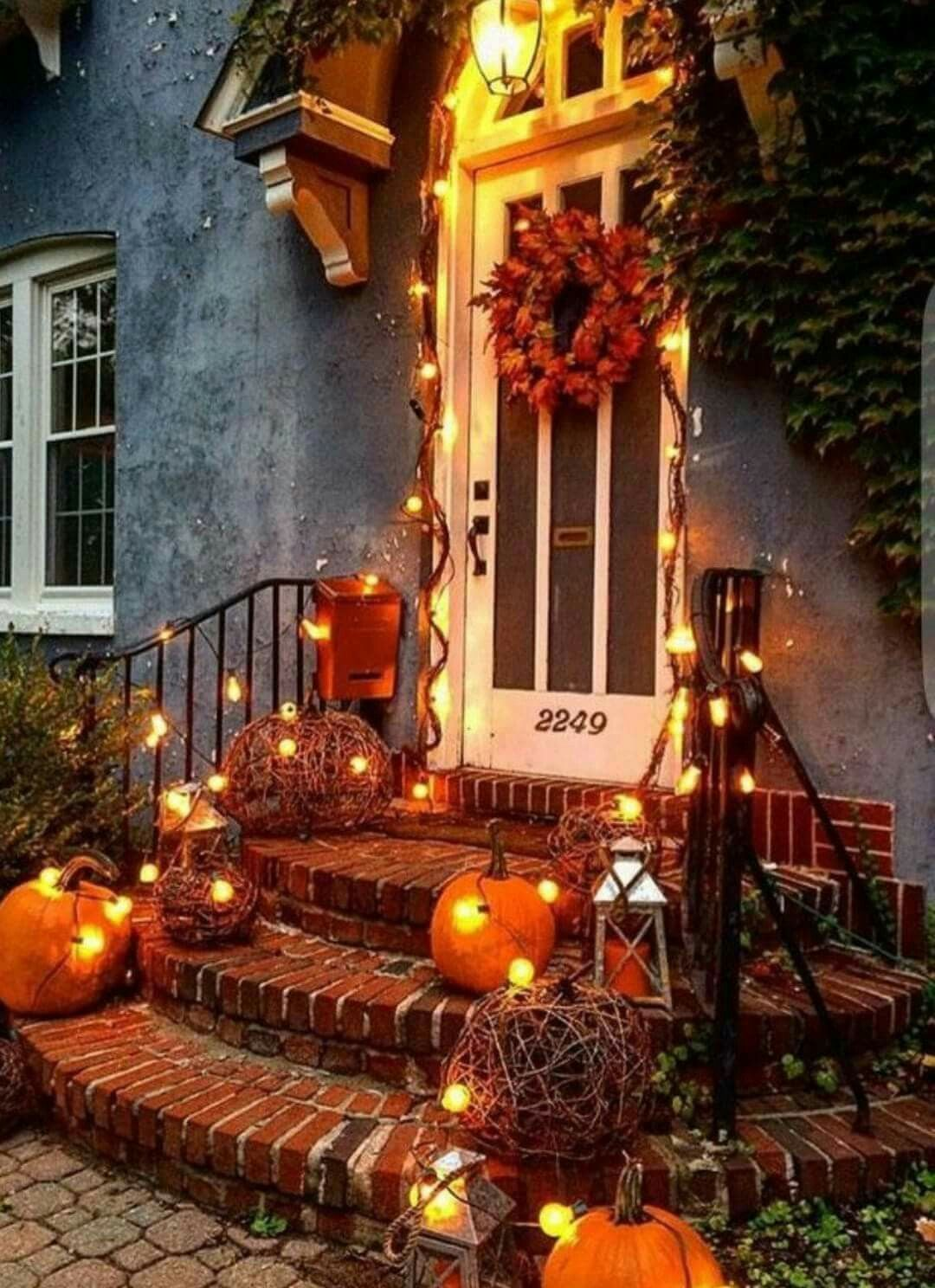 Image shows front door porch with pumpkins and Christmas lights all lite up.
