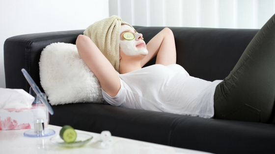 Woman enjoying a spa day at her apartment with a face mask and cucumber eye patches.