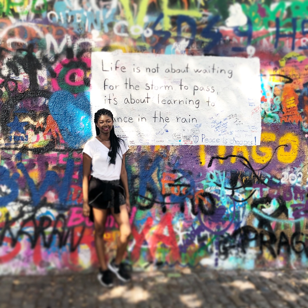 "woman standing in front of john lennon wall with quote ""life is not about waiting for the storm to pass, it's about learning to dance in the rain"""