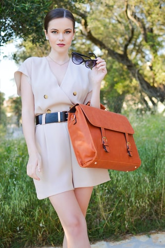 A fashion style woman with orange bag in it.