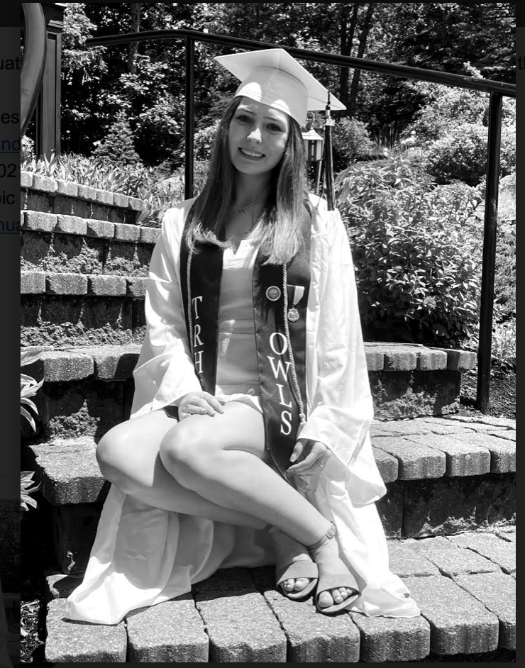 Black and white photo of a graduate wearing a light colored cap and gown
