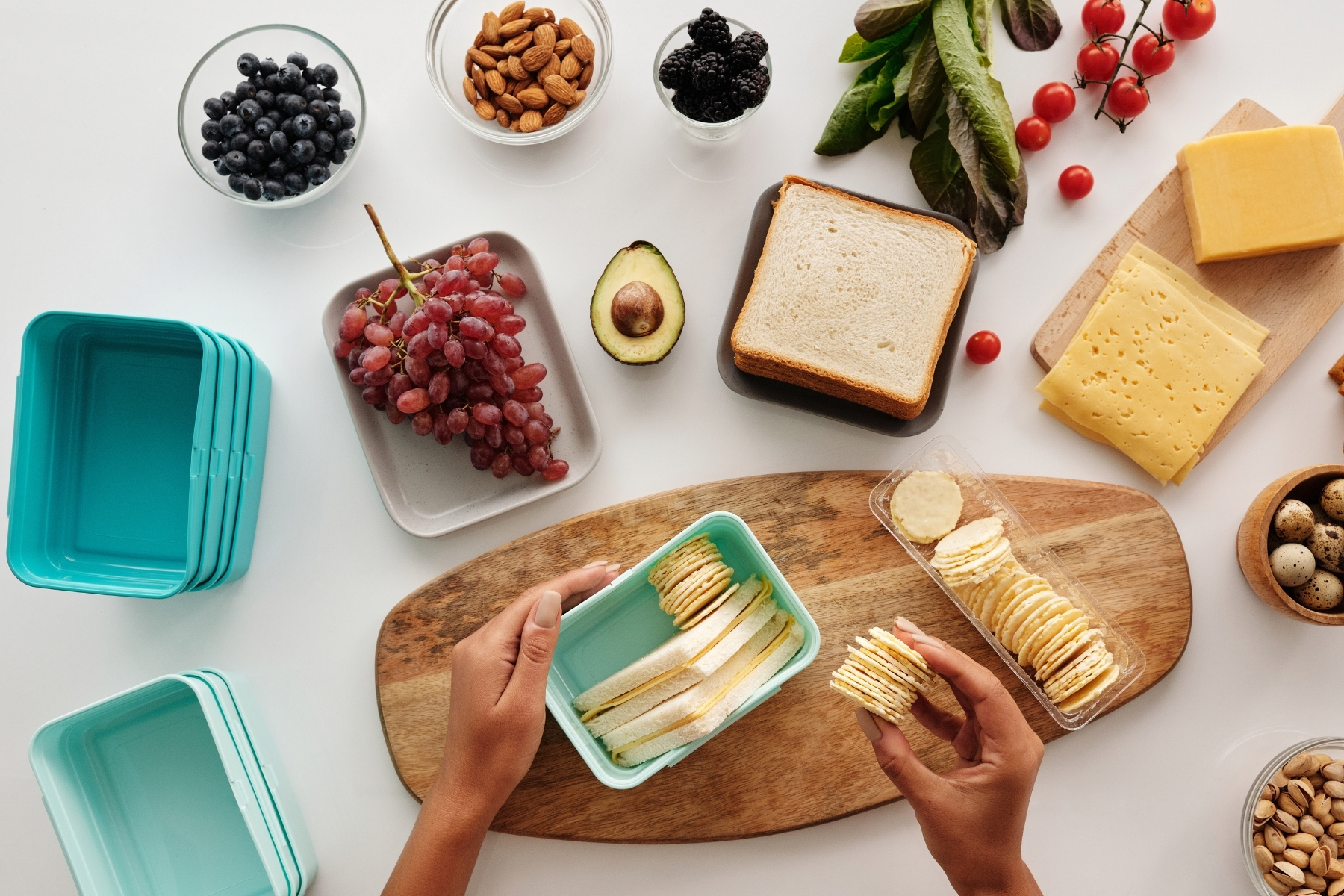 Image of various healthy snacks that could be included in a diet focused on intuitive eating: sandwich, crackers, fruit, cheese, and nuts.