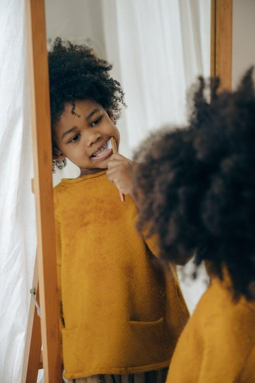 Concentrated black child in yellow sweater cleaning teeth with toothbrush looking at long mirror in bathroom