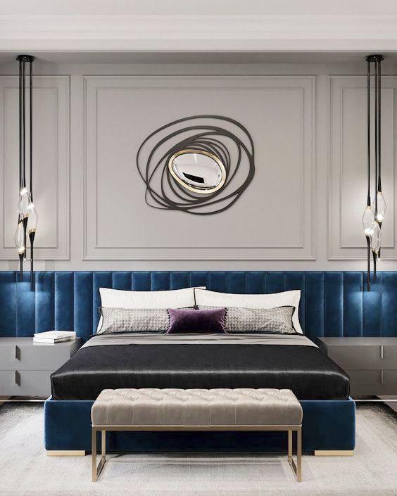 Quarto de casal com cabeceira aveludada azul no comprimento da parede, paredes cinza com espelho de design criativo, banco estofado no pé da cama