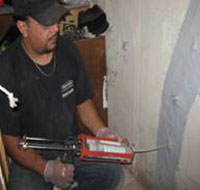 A repair man fixing the crack in the wall