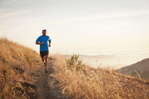 Man running on grassy hillside