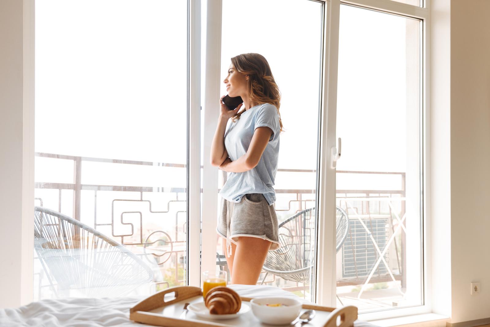 Nő telefonál műanyag toló-bukó teraszajtó előtt