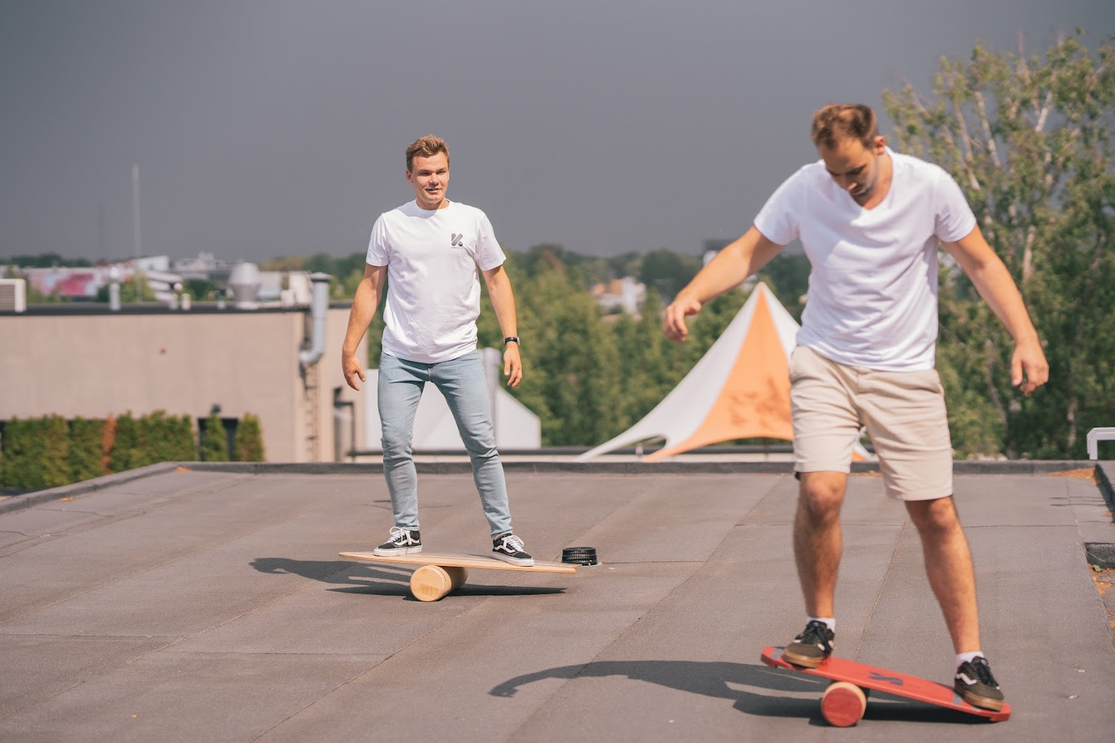 Two people using balance boards on a rooftop