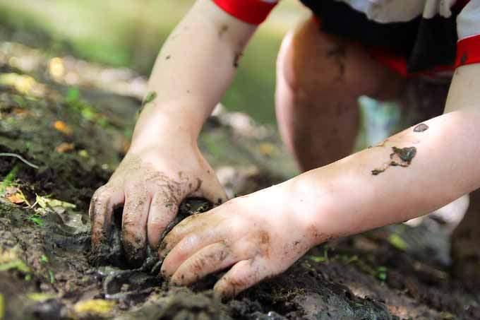 Criança brincando na lama. Mão suja de lama