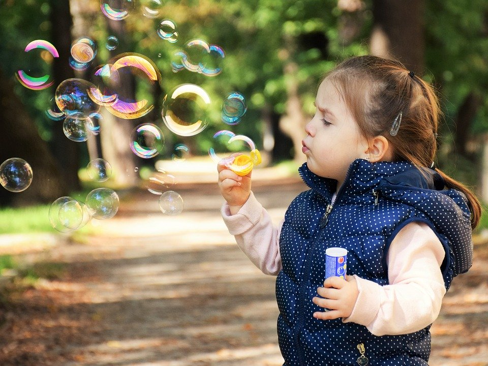 Little girl blowing bubbles outside | Influencers under 10