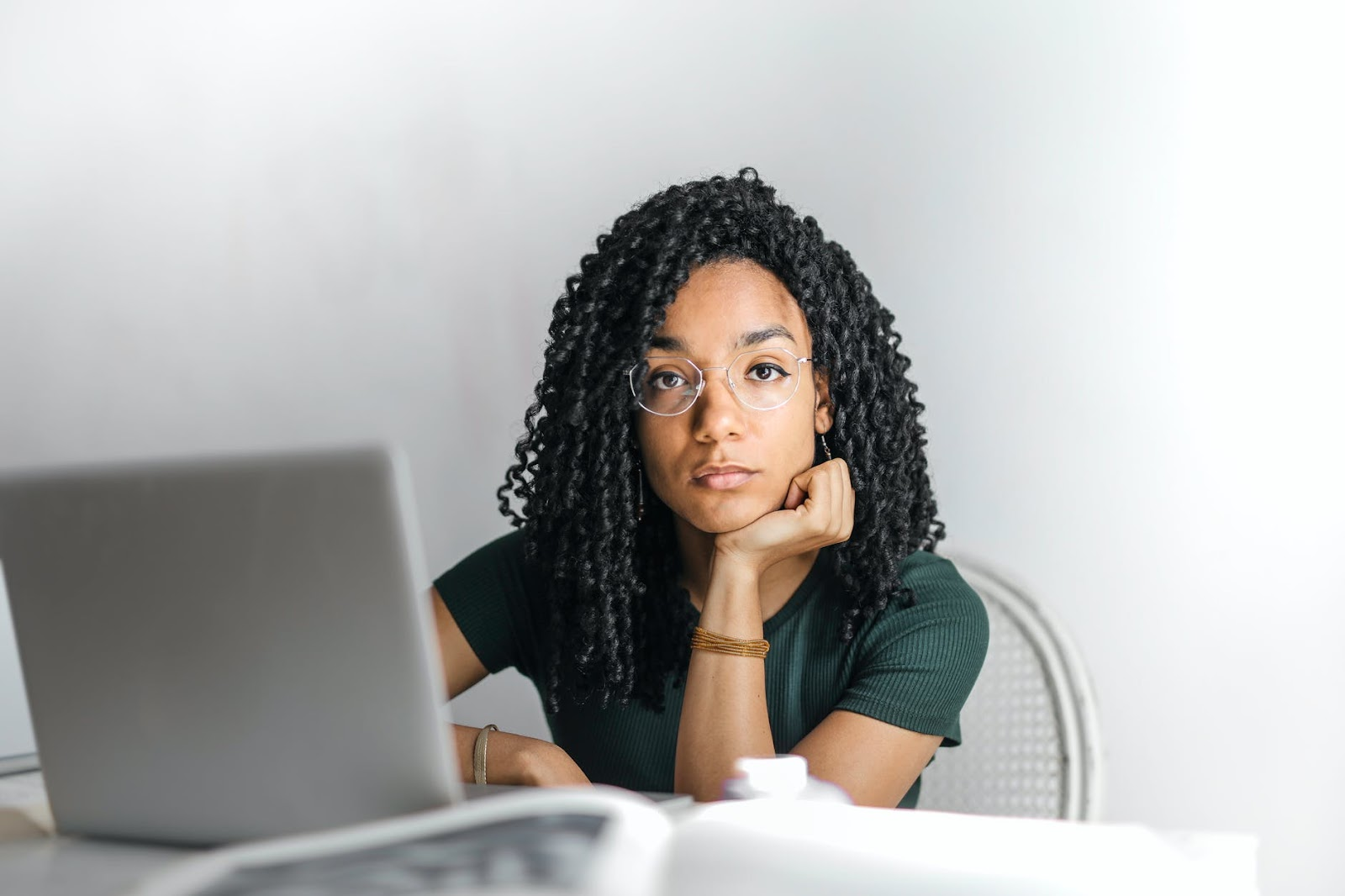 serious-ethnic-young-woman-using-laptop-at-home- contemplating small business preparation basics