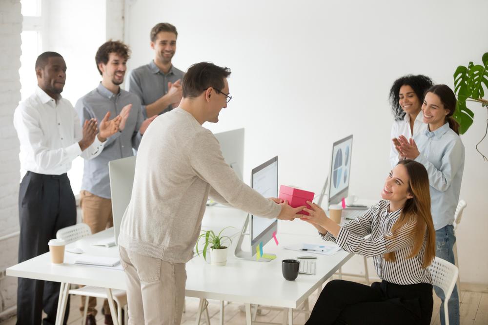 Um homem entregando um presente para uma mulher em uma empresa.