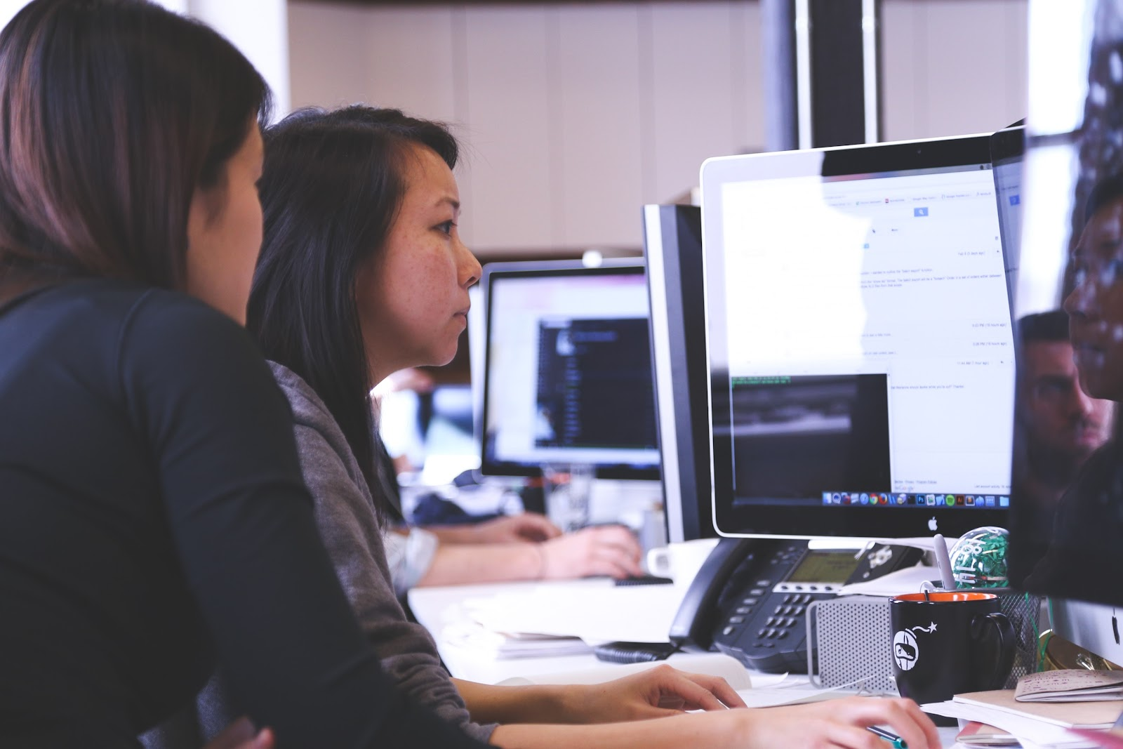 Two women working together in front of the computer