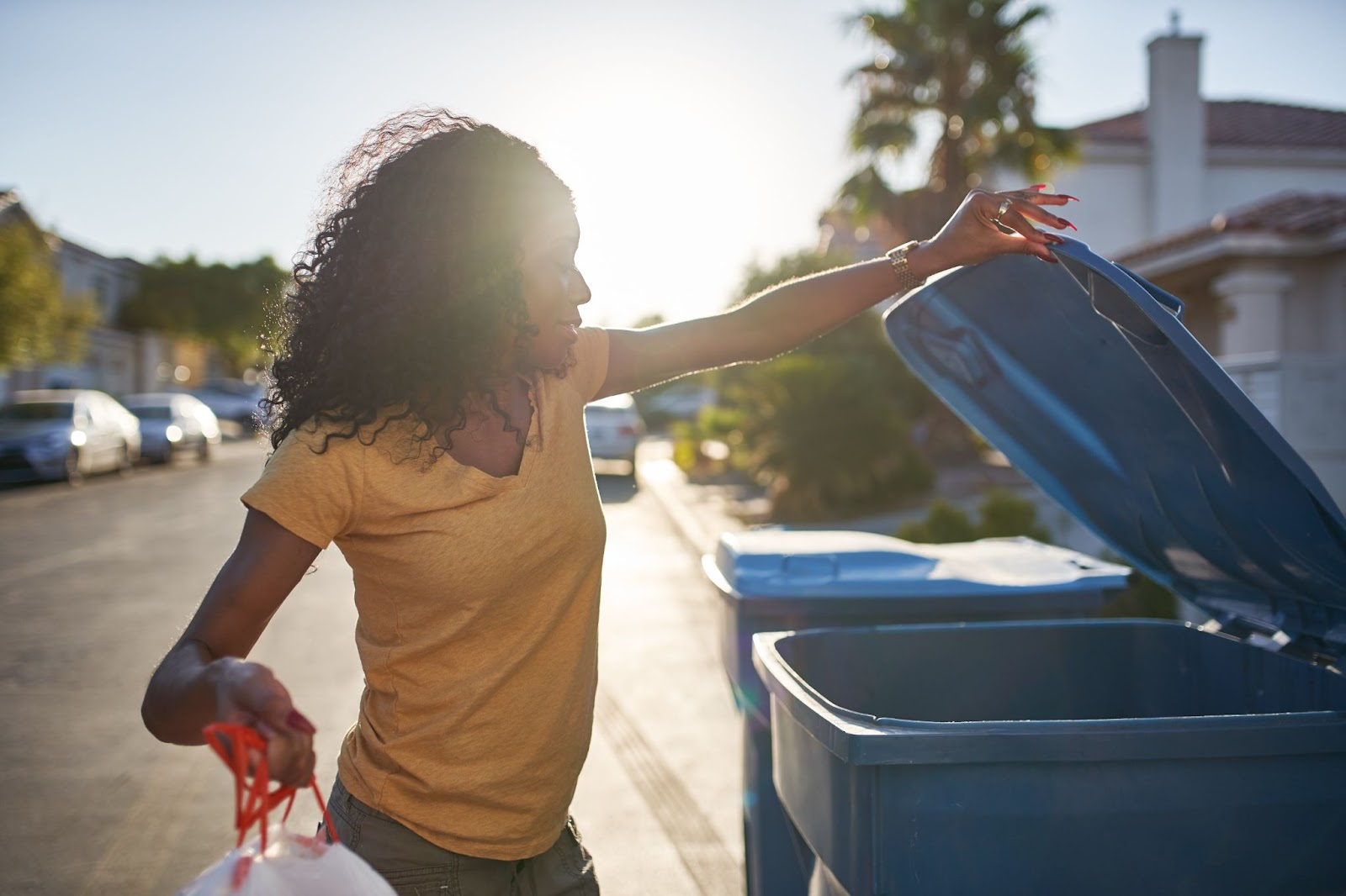 A woman participates in curbside recycling.