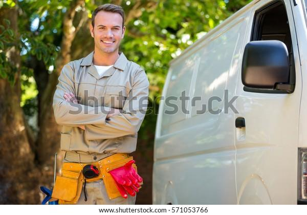 Handyman with tool belt around waist standing next to van
