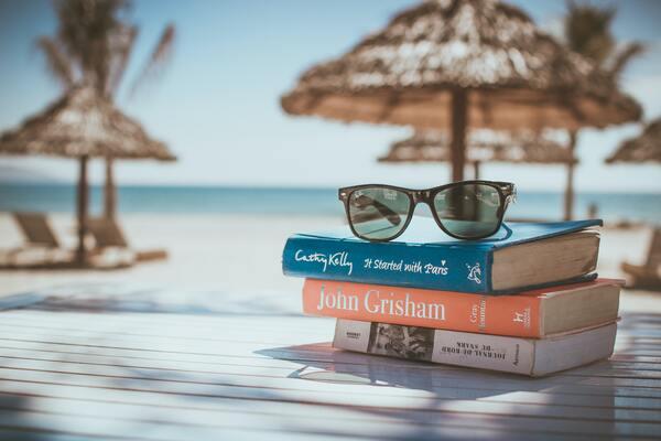 foto de livros e óculos de sol na praia