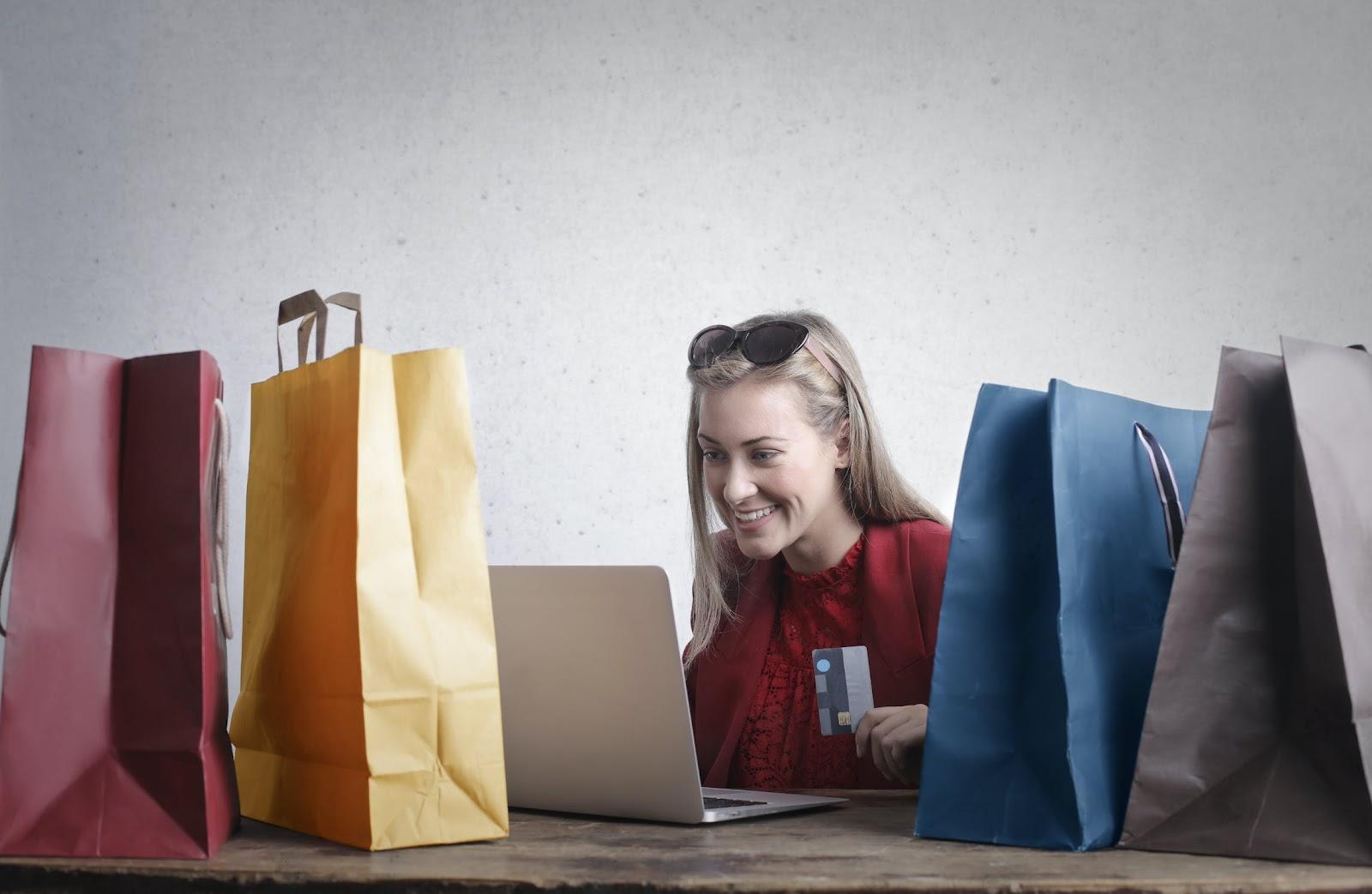 Mulher fazendo compras online, cercada de sacolas de outras compras.