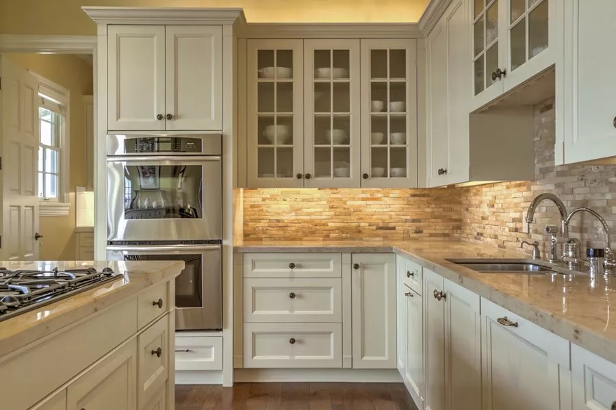 white shaker kitchen with stacked stone backsplash, cabinet lighting, glass door cabinets, stainless steel appliances and marble countertops