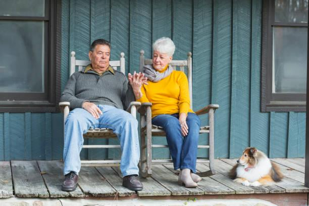 Senior couple sitting on porch, holding hands, with dog A senior couple sitting side by side on their porch on rocking chairs, holding hands. A dog is lying down beside the woman. old person in a rocking chair stock pictures, royalty-free photos & images