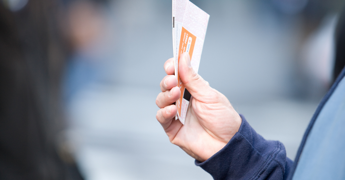 The hand of a man with two tickets in his hand
