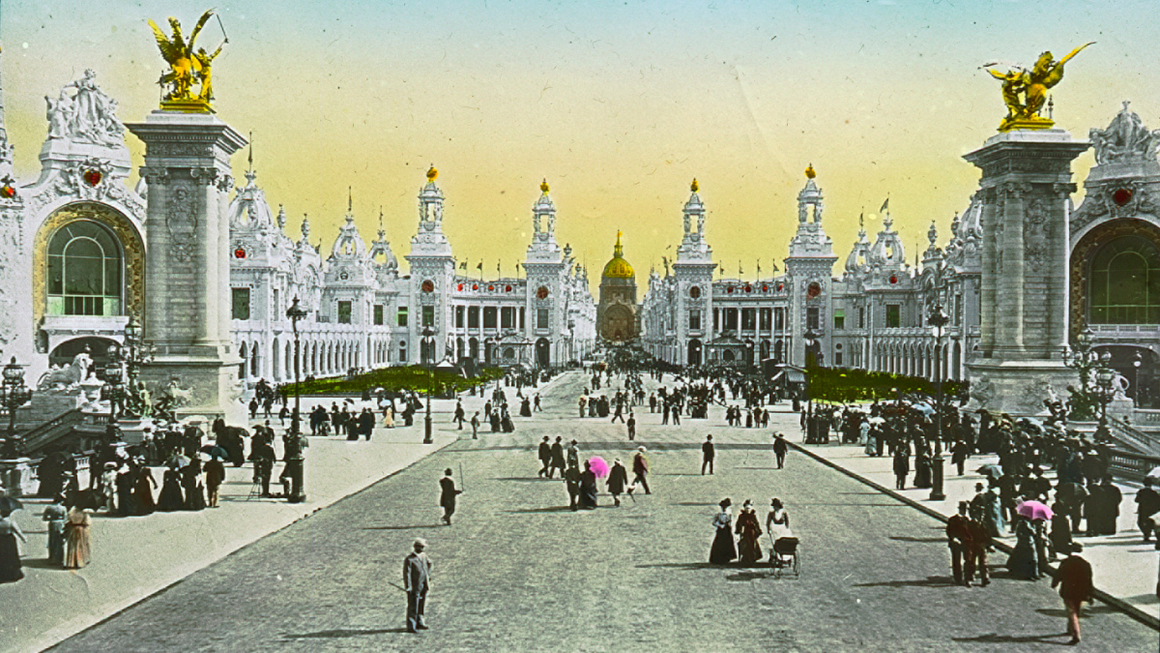 People from the early 1900s taking a stroll in the enormous open thoroughfare of the Paris Exhibition Universelle