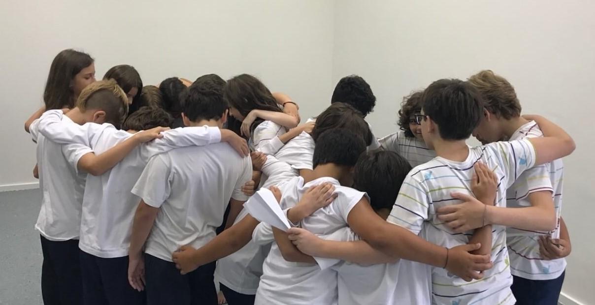 A imagem mostra um grupo de crianças se abraçando.