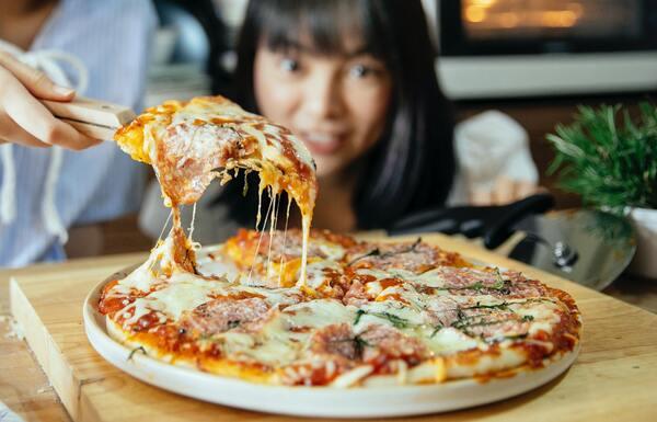 Foto de uma mulher pegando uma fatia de pizza