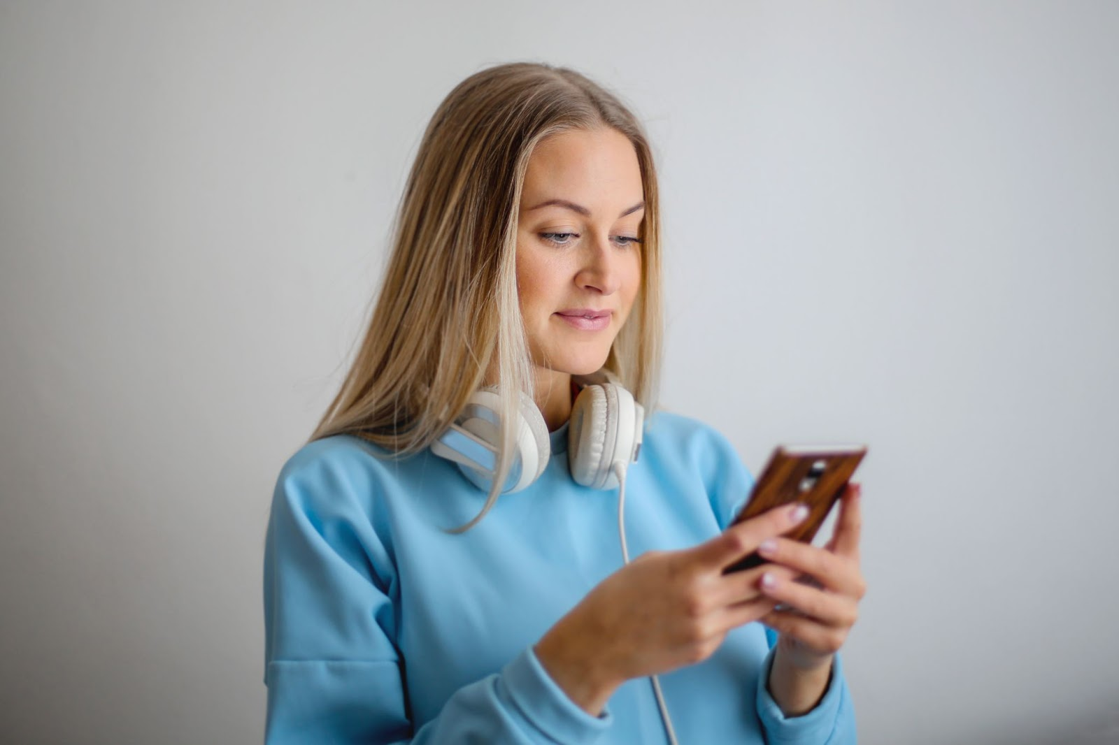 A woman listening to music on her phone -Spotify Tips and Tricks
