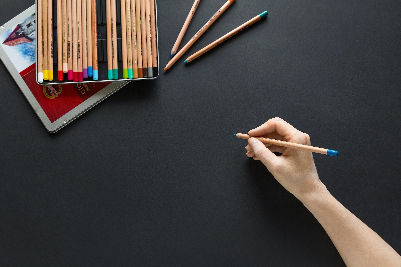 Designer hand holding colored pencil about to design draw