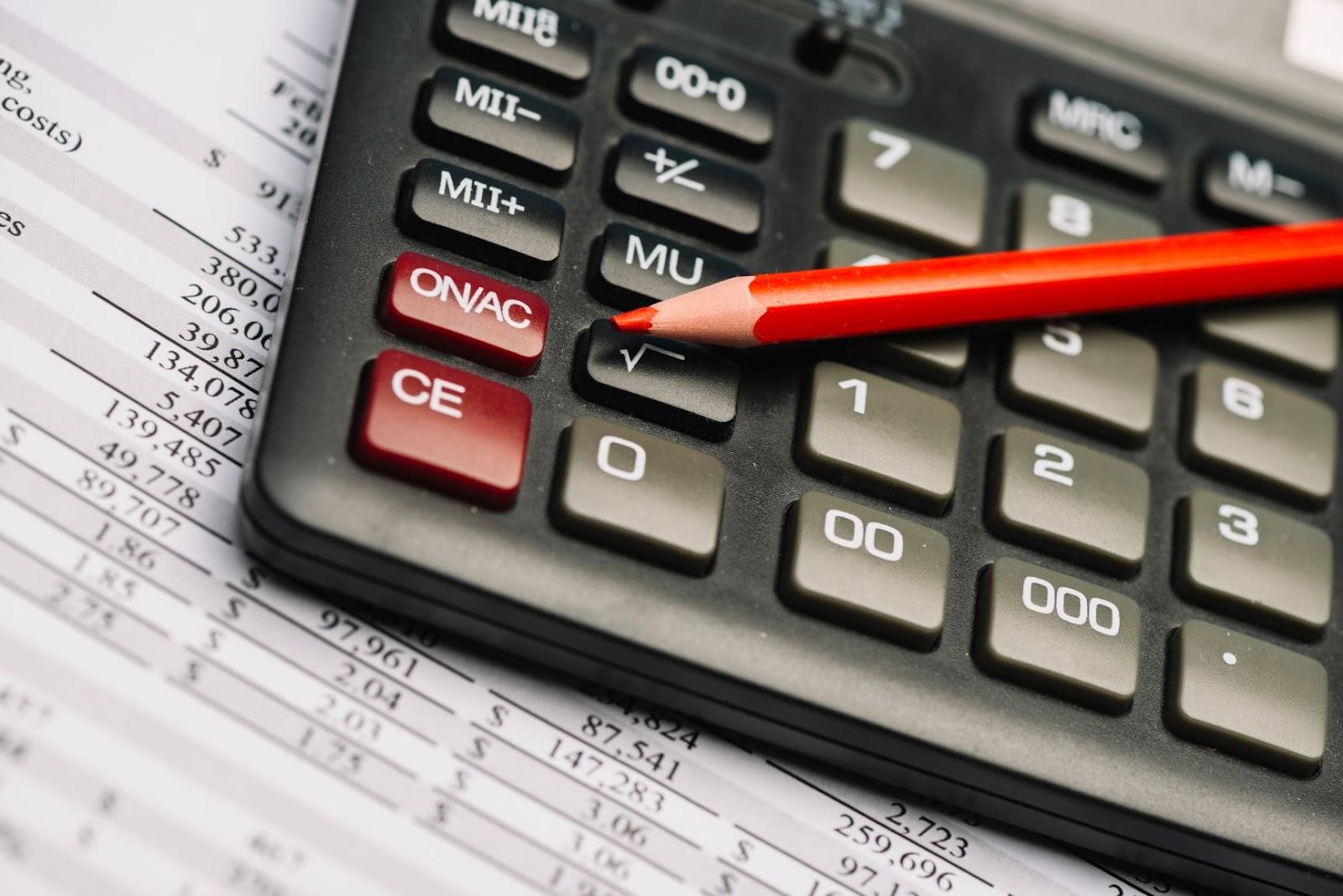 Foto de uma calculadora científica, focada e próxima as principais teclas. A calculadora está acima de um papel impresso, com diversas tabelas e números. Identificamos, em cima das teclas da calculadora, um lápis de cor vermelho. A imagem visa ilustrar a escolha entre eireli ou ltda.