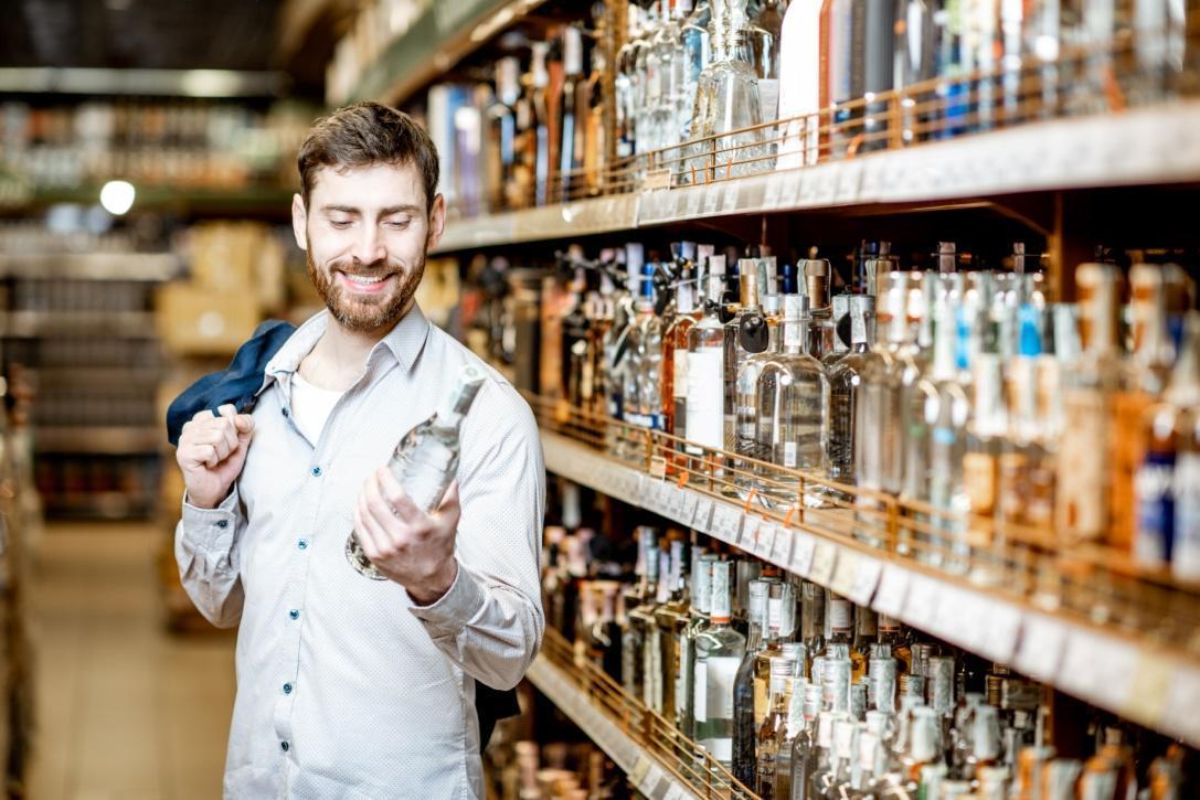 man-choosing-alcohol-in-the-supermarket-73MU53F.jpg