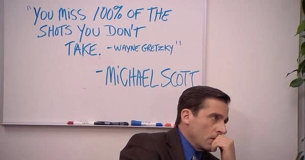 Michael Scott, a character from The Office, sits by a whiteboard with a misattributed aspirational message.