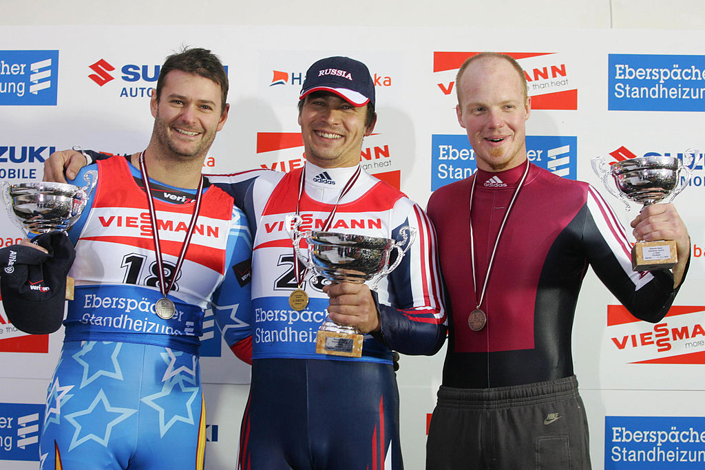 Sigulda, LATVIA: From L to R, second-placed US Tony Benshoof, Russian winner Albert Demtschenko and third-placed Latvian Martins Rubenis pose on the podium of the Luge World Cup men event, 06 November 2005 in Sigulda. AFP PHOTO ILMARS ZNOTINS (ILMARS ZNOTINS/AFP/Getty Images)