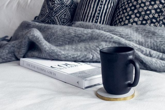 cushions, a throw, a book and a mug on a cozy bed