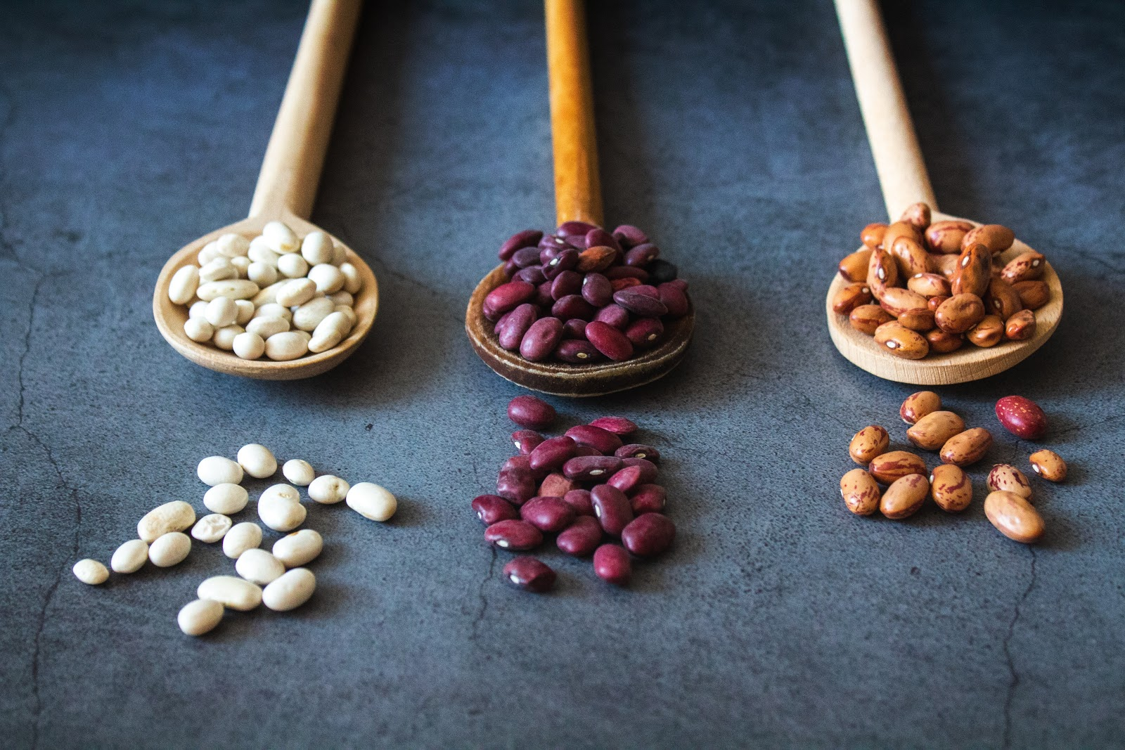 three kinds of beans in wooden spoons