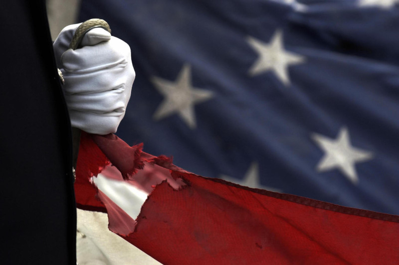 A police officer grips a corner of a torn U.S. flag at a memorial ceremony in New York on Sept. 11, 2004.