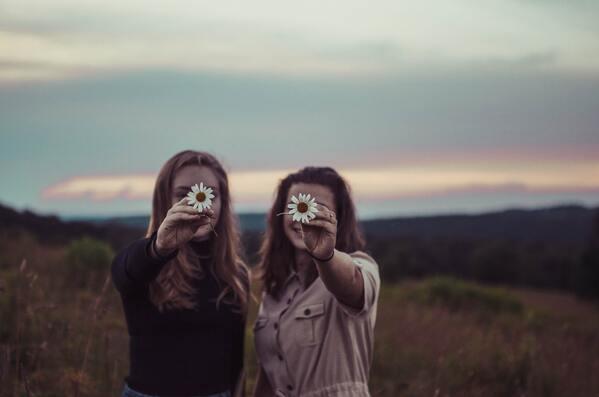 Duas amigas posando com uma flor